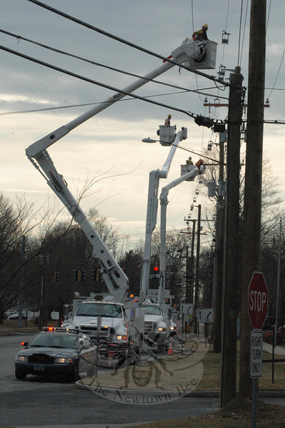 Electrical workers positioned in three bucket-lift trucks rigged some new equipment along Queen Street on Wednesday morning, as police stood by down below and directed traffic through the area. During the past several weeks, electrical crews have been working on Queen Street, Church Hill Road, Glover Avenue, and Sugar Street to position the new electrical equipment that will be needed by the Connecticut Light & Power Company to provide sufficient electricity for Advanced Fusion Systems, a technology firm that is refitting and expanding a factory on Edmond Road.  —Bee Photo, Gorosko