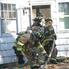 Four volunteer firefighters practiced teamwork in handling a charged fire hose at a vacant house as they performed drills to extinguish interior fires. —Bee Photo, Gorosko