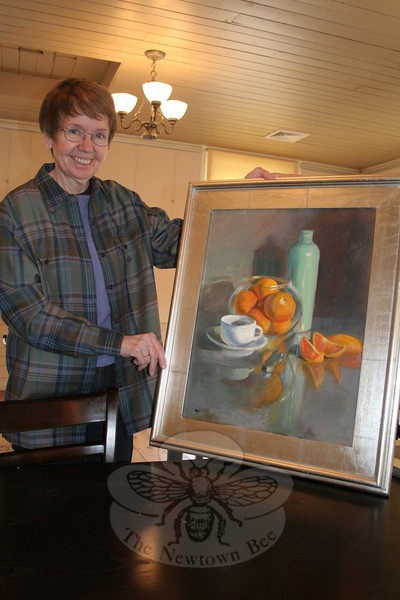 """Art About Town: Stone River Grille"" participating artist Pam Danneman shows off ""Still Life With Oranges,"" one of her original works included in the exhibition. The collection is on view now, and a formal opening reception will be co-hosted by the restaurant and SCAN on Sunday, February 12.		—Bee Photo, Hicks"