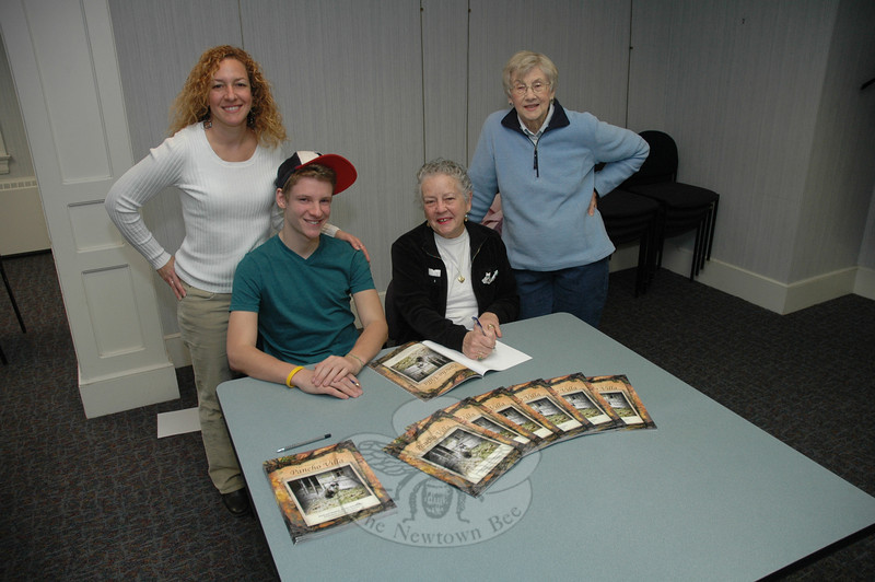 Darlene Jackson, second from right, signs a copy of The Secret Adventures of Pancho Villa: Poems and Memories of Other Beloved Pets (Trafford Publishing, paperback 36 pages, $20) for Peg Forbell, right, at a book signing event Saturday, January 28 at C.H. Booth Library. Looking on are Koren Harpaz, second from left, who illustrated the book, and his mother, Jill Chaus. The book holds a collection of literary works on pets by Mrs Jackson's late husband Donald Dale Jackson.                    —Bee Photo, Gorosko