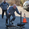 Newtowner Tim Sullivan shoves the prowler sled down the driveway at CrossFit 203 in Danbury during one of the more unusual CrossFit warm up activities, while teammate Frank Milano, also of Newtown, looks on.  —Bee Photo, Crevier
