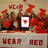 Newtown's Municipal Center and staffers were festively decked out in red Friday, February 3, but their message was a serious one: heart disease is the number one killer of women in the United States. Representatives from Newtown VNA,  Newtown Health District, Board of Education, the town clerk's and the first selectman's offices, including First Selectman Pat Llodra, far left, took a few moments to gather on the American Heart Association's Go Red for Women Day to remind women to be heart healthy. The table display with heart health-related information will remain on view at the municipal center all month.					                 	                                             —Bee Photo, Voket