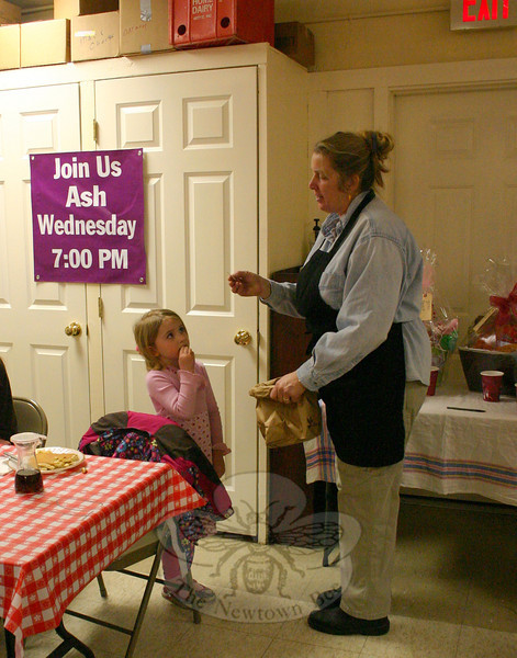 Alexandra Knaggs (left) helped Mary Fellows, right, find winners for five raffle prizes during St John's Shrove Tuesday Pancake Supper. Proceeds from the sales of raffle tickets will be used toward a serenity garden and labyrinth the parish is planning.—Bee Photo, Hicks