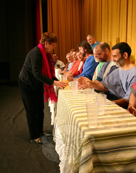 "Immanuel Lutheran Players Stage Manager Jeri Surovy, on the left, is very particular about the placement of each item on the table that is the centerpiece of The Last Supper Enactment. While she is conscientious of the location and look of each item, her one concession to theatricality, she admits, is the striped tablecloth atop a white tablecloth. ""In da Vinci's painting, it is a white tablecloth,"" she said. ""But under the stage lights, all white wouldn't work.""	—Bee Photo, Hicks"