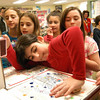 Alexandra Chatzikonscantinou, center, stamps a box at Reed Intermediate School on Friday, February 17, to send through the Valentines For Troops program to troops serving overseas. —Bee Photo, Hallabeck
