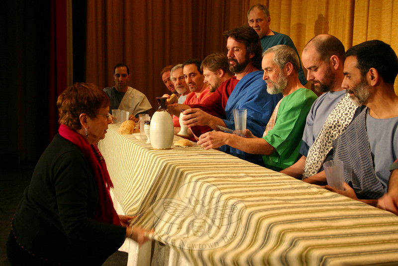 """Immanuel Lutheran Players Stage Manager Jeri Surovy, on the left, is very particular about the placement of each item on the table that is the centerpiece of The Last Supper Enactment. While she is conscientious of the location and look of each item, her one concession to theatricality, she admits, is the striped tablecloth atop a white tablecloth. """"In da Vinci's painting, it is a white tablecloth,"""" she said. """"But under the stage lights, all white wouldn't work.""""—Bee Photo, Hicks"""