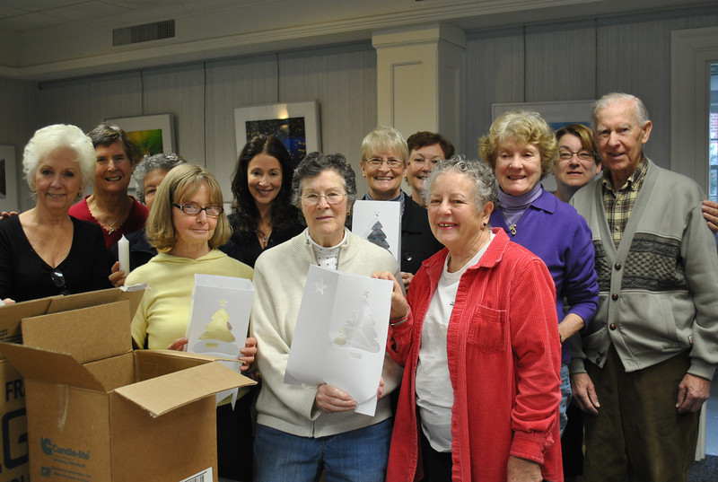 Diana Johnson of the Tree Lighting Committee gathered several community volunteers Monday, November 15, in the meeting room of the C.H. Booth Library, to rebox luminarias — designed and donated by Curtis Packaging of Sandy Hook — and plumbers' candles, for distribution to homeowners in the center of town. The luminarias are placed along the length of Main Street, Glover Avenue, South Main Street, and around Ram Pasture pond on the day of the annual tree lighting in Ram Pasture, scheduled this year for Friday, December 3, at 6:30 pm. The long-burning candles are lit as dusk descends that evening, creating a sparkling scene to greet the hundreds of residents that gather in Ram Pasture to sing, sip cider, and kick off the Newtown holiday season with the lighting of the tall spruce at the edge of Elm Drive. A total of 2,500 luminarias will light the way this holiday season. Pictured from left, front row, are volunteers Maureen Rohmer, Marj Aitchison, and Darlene Jackson; rear row, Evelyn Farrell, Diana Johnson, Joy Kopesky, Edwana Cusick, Chris Reed, Marg Studley, Bobbe Bowles, Colleen Honan, and Alex Aitchison.  (Crevier photo)