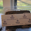 """Mr Cocozza provides corporate """"belly bands"""" for companies that wish to use Bad Louie's Fudge as a promotional gift. Here, a """"belly band"""" for Hilton Hotel wraps around a one-pound container of Bad Louie's Fudge.  (Crevier photo)"""