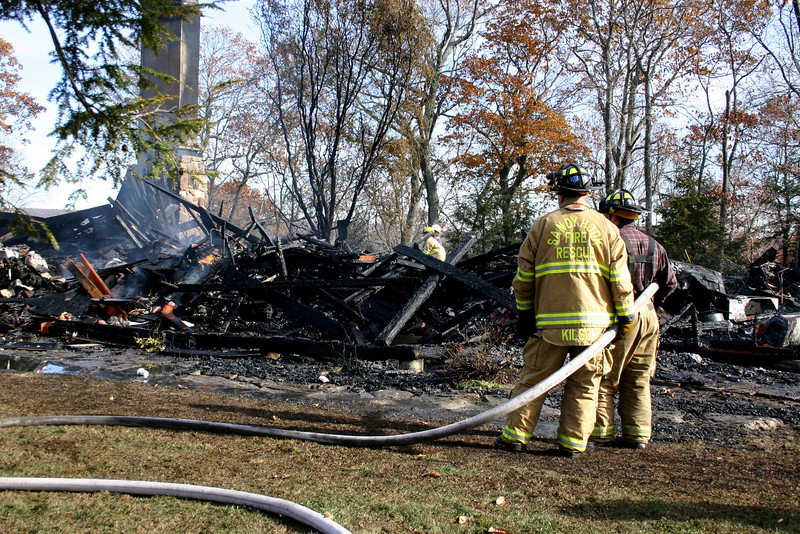 Sandy Hook Volunteer Fire & Rescue Company Firefighters Chuck Kilson and Gabe Blais keep a hose line on a section of the ruins of a house fire that occurred early on the morning of Sunday, November 14, at Zoar Ridge Stables at 5 Morgan Drive in Sandy Hook.  (Bee Photo, Hicks)