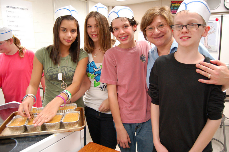 Newtown Middle School family and consumer science teacher Rose Ann Beck stood with seventh graders, from left,  Monica Faust, Sarah Bender, Sean Runkle, and Ryan McIntyre after school on Tuesday, November 16, while the group, along with 24 other students, worked to bake pumpkin bread to add to the Women Involved in Newtown's Thanksgiving baskets.  (Hallabeck photo)