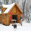 "Susan Snow gave a wave, with her dog Bosco keeping an eye from the yard, from the front porch of a wood shop her husband Glenn built on the couple's Sandy Hook property. Glenn took a plan and modified it, said Susan, and hand cut all of the wood for the building. The building, which took a few years to complete, is a combination of cedar, hickory, birch, oak and maple. ""It's a good representation of Connecticut wood,"" she said. The outbuilding and its flags provided a beautiful spot of color on February 24, which dawned gray and dull af-ter an early morning snow. While the frozen precipitation had stopped by daybreak, and late morning and afternoon rains quickly washed away much of the snow, but for a few hours it looked like winter again in Newtown.   (Hicks photo)"