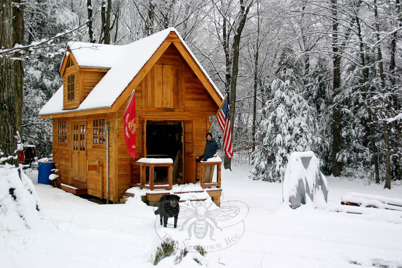 """Susan Snow gave a wave, with her dog Bosco keeping an eye from the yard, from the front porch of a wood shop her husband Glenn built on the couple's Sandy Hook property. Glenn took a plan and modified it, said Susan, and hand cut all of the wood for the building. The building, which took a few years to complete, is a combination of cedar, hickory, birch, oak and maple. """"It's a good representation of Connecticut wood,"""" she said. The outbuilding and its flags provided a beautiful spot of color on February 24, which dawned gray and dull af-ter an early morning snow. While the frozen precipitation had stopped by daybreak, and late morning and afternoon rains quickly washed away much of the snow, but for a few hours it looked like winter again in Newtown.   (Hicks photo)"""