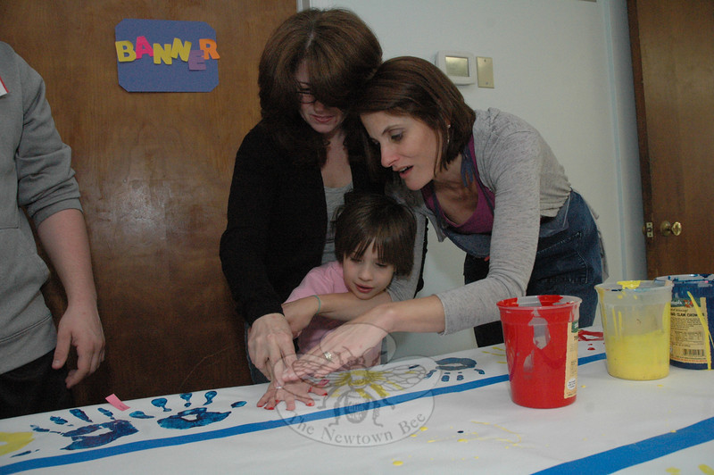 Young Sarah Rothenhausen's right hand is guided by her mother Laura and by Suzanne Lang, right, as Sarah makes a palm print on a poster being created for display during Autism Awareness Month. (Gorosko photo)