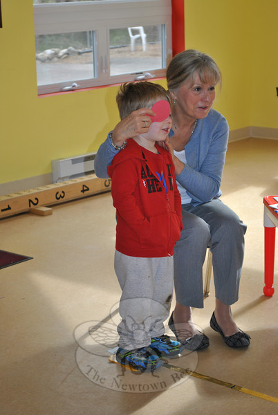 Newtown Volunteer Nurse Association (VNA) board member Rebecca Smith holds a patch over the eye of 3-year-old Mason Moody, Thursday, March 29, at the Children's Adventure Center, as she assesses his visual acuity. Certified VNA members provide eye screening for children in several Newtown preschools each spring and summer, working through the Prevent Blindness Tri-State program. The local VNA has provided this service for more than 20 years, and has successfully identified numerous 3-year-olds who can benefit from a follow-up eye exam by a professional. According to Ms Smith, one in 20 preschoolers may have a vision problem. The free eye screening is one of many health screenings the Newtown VNA provides to the community.  (Crevier photo)