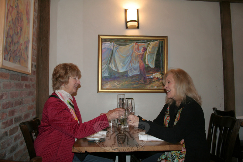 Marianne Scanlon, left, and Rosemary Rau lift their glasses in a toast on Tuesday, April 3, at Stella Restaurant and Bar. The women were part of a small team of SCAN curators who hung two new shows and added new works to a third show, all within the past week. The exhibition at Stella, a relatively new restaurant in Bethel, is the first in a new location for SCAN.  (Hicks photo)