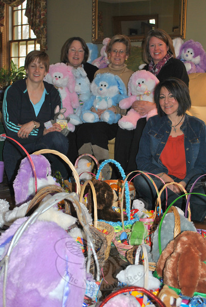 Surrounded by filled Easter baskets and stuffed animals are WIN members, from left, Wendy Delehanty, Peggy Velthuizen, Cindy Gallatin, Denise Tramposch, and Lisa Burbank. WIN members spent several hours, Thursday, March 29, assembling Easter baskets for delivery to area social service organizations, which in turn see that needy children receive them.   (Crevier photo)