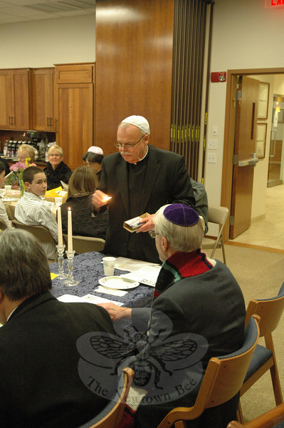 Monsignor Robert Weiss lit a candle as part of the ceremonial Seder.  (Gorosko photo)