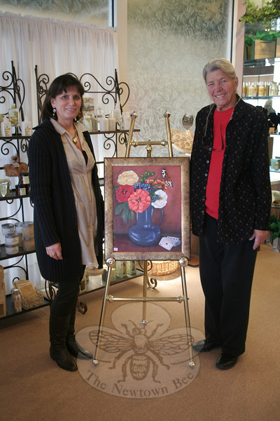 "Melanie Allen, the owner of Avancé Esthétiques Day Spa, left, and Virginia Zic stand in the front area of the day spa in Sand Hill Plaza on Monday, April 2, after a new exhibition of works by members of The Society of Creative Arts of Newtown was installed. Between the women is ""Ace of Spades"" by Ann Marie Foran.  (Hicks photo)"