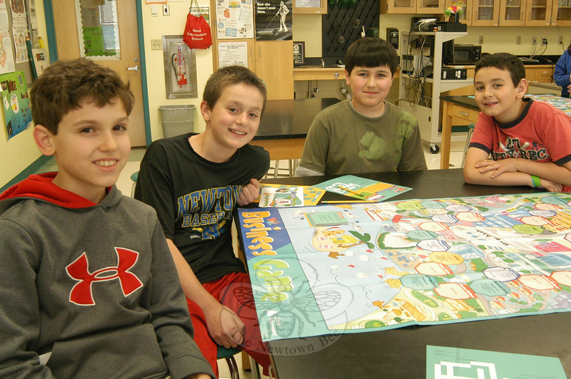 """From left, Michael Arther, Robert DiSibio, Alex Wong, and Matthew Blanco set up """"Business Game"""" to play on Monday, April 2, during the final class for Reed Intermediate School's Junior Achievement program this school year.  (Hallabeck photo)"""