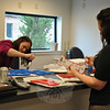 NYFS Executive Director Candice Foster, left, and community coordinator Kaitlyn Johnson add the finishing touches to letters that will decorate the walls of the children's waiting area, Wednesday morning, April 11, at the agency's new quarters at 15 Berkshire Road, in preparation for the Monday, April 16 opening.   (Crevier photo)
