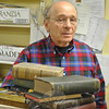 Friends of the C.H. Booth Library volunteer Pete Stern peers over a stack of used books donated for the 2012 book sale. He and fellow book sale volunteers are beginning to look at how the future of the Annual Book Sale that generates more than $100,000 for the library each year may change. They anticipate that the increasing popularity of e-readers, movie streaming, and downloading of music onto personal devices means that fewer books, DVDs, and CDs will be donated to the sale in future years. The donation of current books is becoming a rarity already.   (Crevier photo)