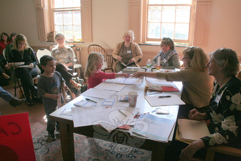 Mason Johansen and Madeline Hart made a brief appearance at the Visiting Nurse Association of Newtown meeting on April 2, presenting the first Volunteers pins on behalf of The Children's Adventure Center. Seated at the table, from right, were VNA President Deb Osborne, Recording Secretary Carol Garbarino, Corresponding Secretary Maureen McLaughlin, and First Vice President Anna Wiedemann.  (Hicks photo)