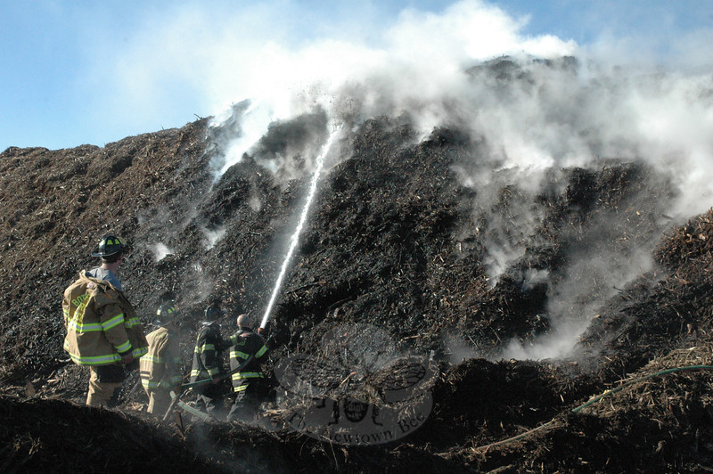 A group of Botsford volunteer firefighters manned a fire hose on the morning of Friday, April 6, in working to extinguish a fire caused by spontaneous combustion within a massive woodchip pile at the town's waste transfer station off Ethan Allen Road.   (Gorosko photo)