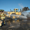 Two Botsford volunteer firefighters doused a pile of burning woodchips near a loader at the town's waste transfer station on the morning of Friday, April 6. The fire, which was caused by spontaneous combustion, was first reported at about 5:30 am that day.  (Gorosko photo)