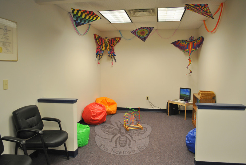 Brightly colored accessories, toys, and a computer fill the separate children's waiting area, located off of the main reception room, in the new NYFS space.   (Crevier photo)