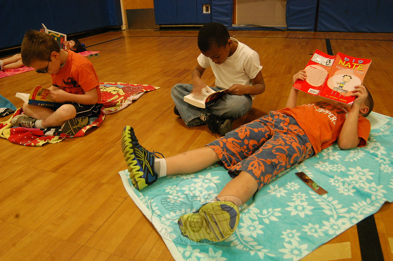 "From left, Middle Gate first graders Jack Corigliano, Khalil Vessup, and Thomas Cornett read in the school's gymnasium on Friday, April 13, for a ""books on the beach"" event.   (Hallabeck photo)"