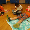 """From left, Middle Gate first graders Jack Corigliano, Khalil Vessup, and Thomas Cornett read in the school's gymnasium on Friday, April 13, for a """"books on the beach"""" event.   (Hallabeck photo)"""