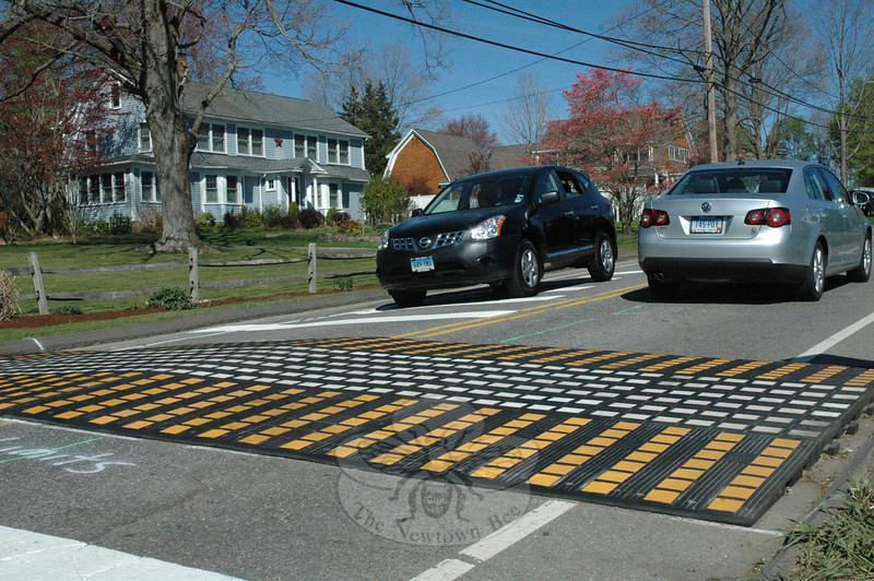 Town workers installed this temporary speed table on Queen Street, just north of its intersection with Lovell's Lane, on Monday. Two speed tables were installed on Queen Street this week in an experiment designed to get motorists to slow down on the northsouth street that links Church Hill Road to Mile Hill Road.  (Gorosko photo)