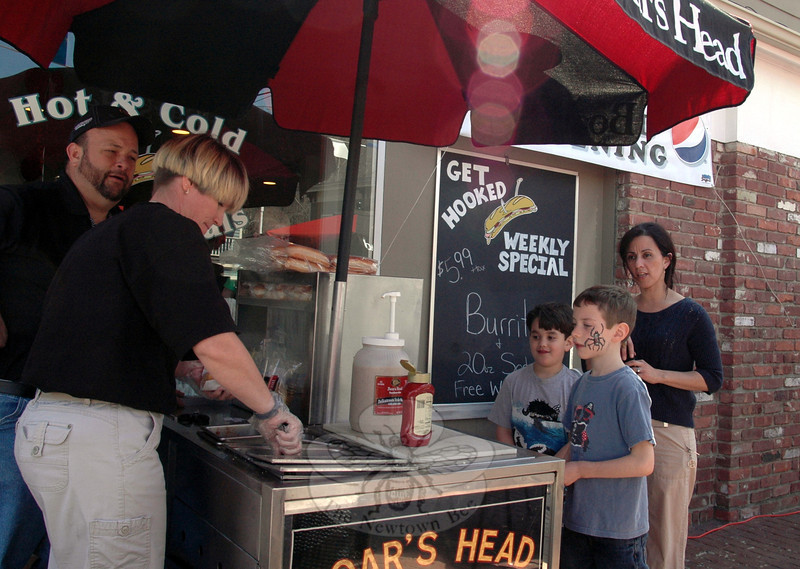 Terry Schott and Cheryl Waters drew a crowd doling out free franks to visitors including Marco Praino and Elliot Ullman, both age 7, during the grand opening of Sandy Hook Deli & Catering on April 14.   (Voket photo)