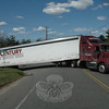 The driver of a New Jersey-based New Century Transportation, Inc, tractor-trailer truck learned about 10:50 am on Friday, April 13, that the geometry of the Toddy Hill Road-Berkshire Road intersection in Sandy Hook is tough, especially when hauling a 53-foot-long trailer over the sharp grade at that sharply angled fork in the road. The driver attempted to make a hard right turn from northbound Toddy Hill Road onto eastbound Berkshire Road, but the retracted landing legs on the trailer got jammed onto the pavement, lifting the trailer's right rear wheels off the ground, thus immobilizing the vehicle. Police halted through-traffic on Berkshire Road between its intersections with Toddy Hill Road and Pole Bridge Road until repair crews could free the truck about an hour after it had gotten stuck.   (Gorosko photo)