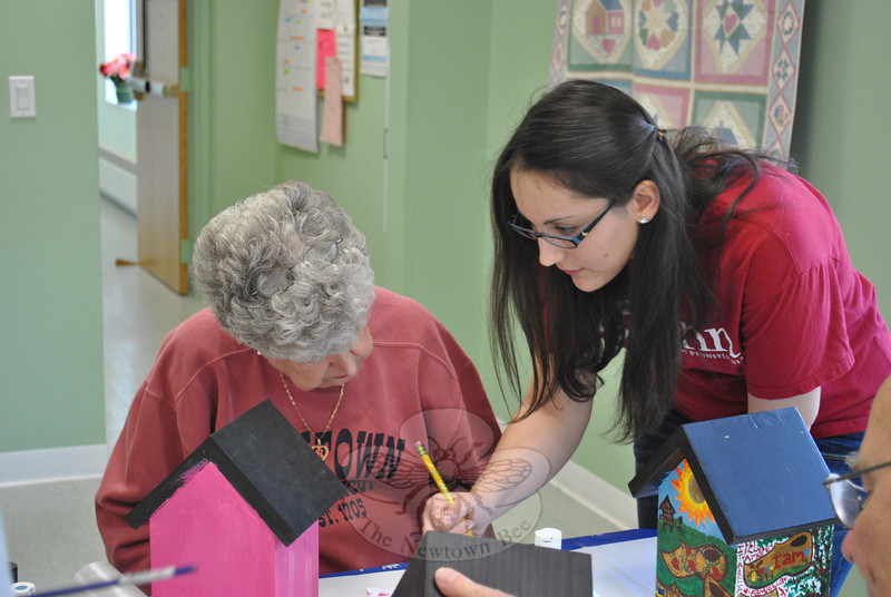 NHS junior Rachel DiVanno advises Newtown Senior Center member Rose Cipolla on design application during a workshop planned and overseen by Rachel on April 19 for her junior/senior John Audubon Birdhouse project.  (Crevier photo)
