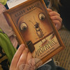 "A Reed Intermediate School student holds a copy Easton author Elise Broach's ""Masterpiece,"" a 2012 Nutmeg Book Award nominee, on April 11.    (Hallabeck photo)"