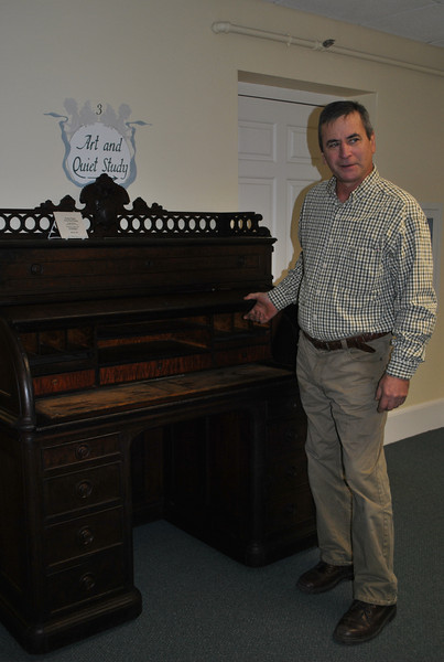 Southbury cabinetmaker and former Newtown resident Greg McAvoy stands next to the mid-1800s rolltop desk he recently refurbished for the library. The Civil War era desk was donated last year to the library.  (Crevier photo)