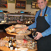 David Beauregard, director of operations at The Meat House in Plaza South, stands next to a display of breads from Wave Hill Breads of Wilton and Chaves Bakery of Bridgeport. Samples of Ariston olive oil and balsamic vinegar are a perfect complement to the freshly baked breads. (Crevier photo)