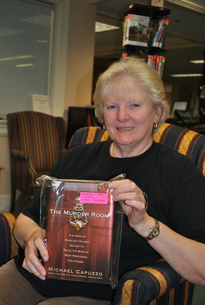 Friends of the C.H. Booth Library Holiday Book Sale coordinator Marge Gingolaski shows off one of two signed copies of The Murder Room by Michael Capuzzo that will be sold at the December 4-5 sale.  (Crevier photo)