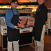"The Meat House employee Bruno Carmo, left, holds a tray of Cowboy Steaks, a bone-in ribeye steak. Scott Ireland, from the Meat House corporate headquarters, displays a tray of T-bone steaks, known as the ""celebratory"" steak.  (Crevier photo)"