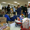 """Mandy Monaco, second from right, and Cyndy DaSilva used wagons to pull donated items from the lower parking lot into the meeting room of Newtown United Methodist Church on Friday, November 19. The women co-chaired the annual Women Involved in Newtown (WIN) Thanksgiving Food Drive, which actually provides food to Newtown families for the period from Thanksgiving until the end of the year thanks to donations from groups, families and businesses across town. WIN works with Newtown Social Services to collect, organize, and then distribute the food. According to Social Services Director Ann Puccini, 76 families were helped through the Thanksgiving program this year. """"We've already helped another eight families today with food for the holidays,"""" Mrs Puccini said on Monday, November 22, """"and these were folks who didn't get on the list for last Friday."""" Any donations that can be offered to Social Services will be """"gladly accepted and appreciated,"""" said Mrs Puccini, who works year-round to provide food to residents.  (Hicks photo)"""
