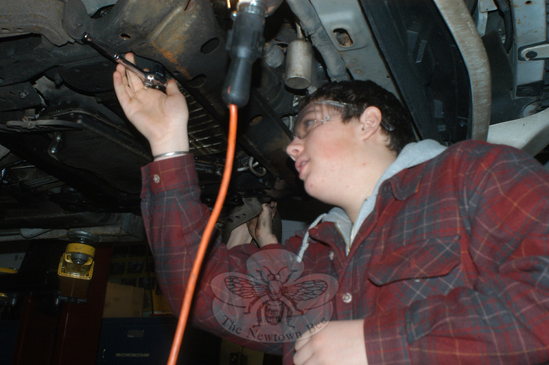 Nick Fatse works underneath a car on the lift at Newtown High School.   (Hutchison photo)