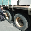Newtown Police Patrol Officer Jeffrey Silver, who is a commercial truck inspector for the town police department, checks some truck wheels at a truck inspection project on May 18 that municipal police from Newtown, Monroe, and Trumbull conducted with state Depart-ment of Motor Vehicles truck inspectors.    (Gorosko photo)