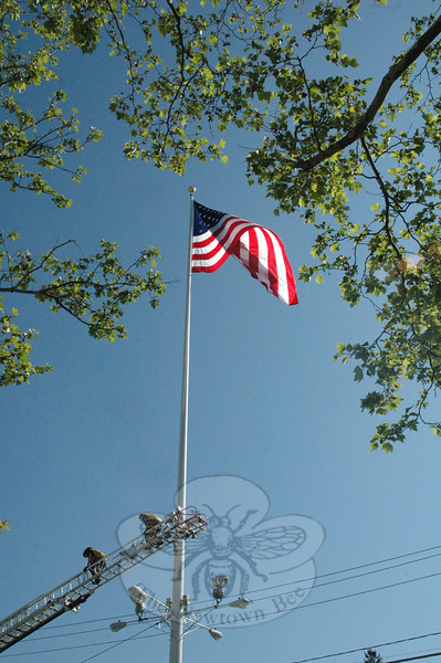 Two Newtown Hook & Ladder volunteer firefighters, who had assisted with hoisting the large summer flag up the Main Street flagpole, walk down the fire company's aerial ladder after securing the large flag on the flagpole. (Gorosko photo)