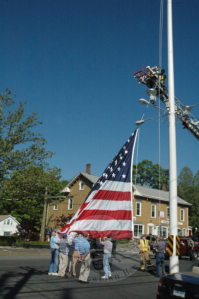 Resident David Lydem, right, who is known as The Keeper of the Flag and Pole, handles the tackle as members of the Newtown Lions Club prepare to loft the large summer flag that flies on the Main Street flagpole. Newtown Hook & Ladder firefighters assisted at the May 19 event at which a 216-square-foot winter flag was replaced by a 600-square-foot summer flag.    (Gorosko photo)