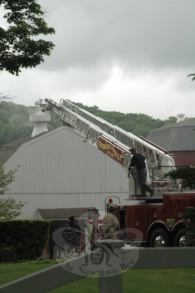 Firefighters from all five local volunteer fire companies responded to two accidental fires that occurred at a barn at the Krueger property at about 9:27 am on Wednesday, May 23, at 41 Flat Swamp Road in Dodgingtown. Two small fires occurred after a person there was attempting to use a portable torch to remove some weeds outdoors next to the barn. There were no injuries. The fires caused an estimated $5,000 worth of damage, according to Fire Marshal Bill Halstead. As seen from Flat Swamp Road, Newtown Hook & Ladder's aerial ladder was extended to the barn.   (Gorosko photo)