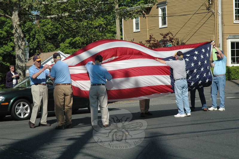 Members of the Newtown Lions Club stood on Main Street on the morning of Saturday, May 19, while folding the winter flag that had just been lowered from the Main Street flagpole, where it had flown since last fall.   (Gorosko photo)