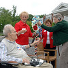 Seated during a veterans' Memorial Day Picnic and ceremony at Masonicare at Newtown is former first selectman and facility resident Jack Rosenthal. Also living at the facility is veteran Nick Kostuk, fixing an honorary wreath to the post with help from First Selectman Pat Llodra, center, and Masonicare Director of Nursing Patti Russell.   (Bobowick photo)