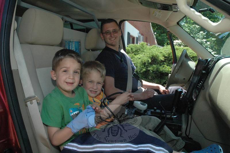 Seated inside a paramedic's vehicle, twin brothers Brian, left, and Stephen Sibley, age 4½, visited with paramedic Bart Piekarski at an open house Saturday, May 19, at the Newtown Volunteer Ambulance Corps garage. The boys are the sons of Barbara and Rob Sibley of Sandy Hook. (Gorosko photo)