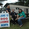 Dogs that are at least six months old must be licensed by the town. June is the month designated for annual dog licensing. Dog licensing is performed from 8 am to 4:30 pm on Mondays through Fridays at the town clerk's office at Newtown Municipal Center, 3 Primrose Street. Current rabies vaccination certificates must be presented when a dog is licensed. The town clerk's office will sponsor a rabies clinic on June 16. The presentation of spaying and neutering certificates allows dogs to be licensed at a fee of $8. However, dogs that are unaltered have licensing fees of $19. During the first week of July, the town clerk's office will hold a drawing to determine the #1 Dog of Newtown. The winner of the drawing will receive the dog tags bearing the #1 for the coming year. Dog licenses may be ordered by mail. For details on ordering a license by mail, contact the town clerk's office at 203-270-4210. Pictured at the town dog pound on May 30 are, from left, Municipal Animal Control Officer Carolee Mason, Kennel Keeper Matt Schaub, and Town Clerk Debbie Aurelia. Mr Schaub is holding Lucky, a male Akita mix, who is suitable for adoption.  (Gorosko photo)